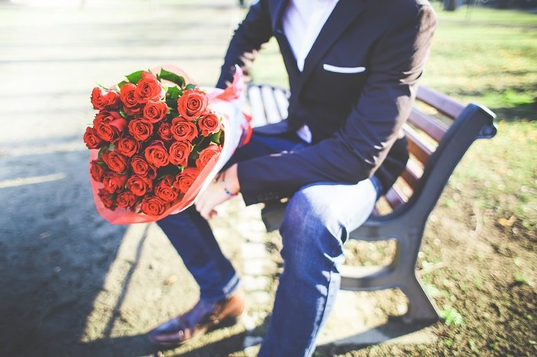 Young man holding a bouquet of red roses